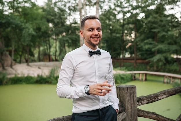 Jonge man met een glas wijn op het zomerterras in het café