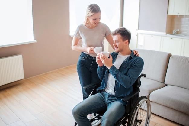 Jonge man met een handicap zit op rolstoel. persoon met speciale behoeften. kopje koffie samen met vriendin houden. ze staat opzij en houdt haar hand op zijn schouder.