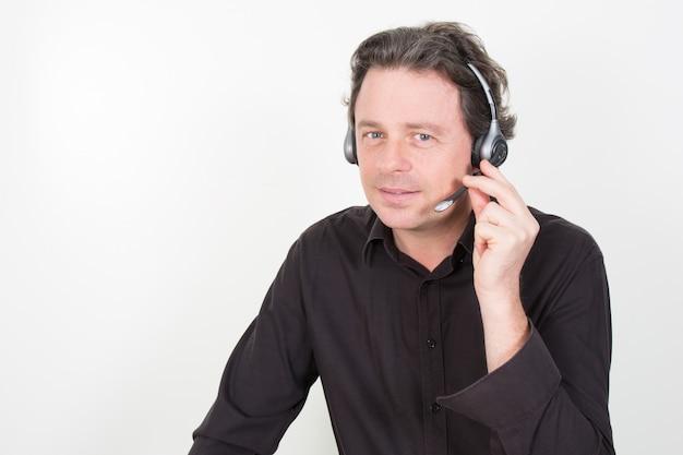 Jonge man met een headset aan tafel zit