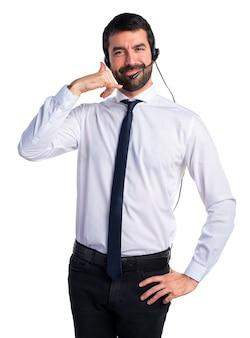 Jonge man met een headset die telefoongebaar maakt