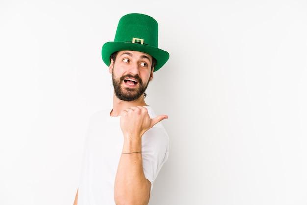 Jonge man met een heilige patricks hoed geïsoleerde punten met duim vinger weg, lachen en zorgeloos