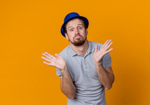 Jonge man met een hoed vieren verjaardagsfeestje op zoek verward armen naar de zijkanten over oranje