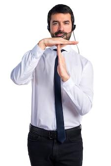 Jonge man met een hoofdtelefoon die tijd uit gebaar maakt