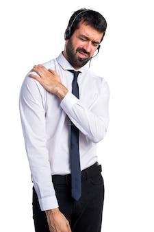 Jonge man met een hoofdtelefoon met schouderpijn