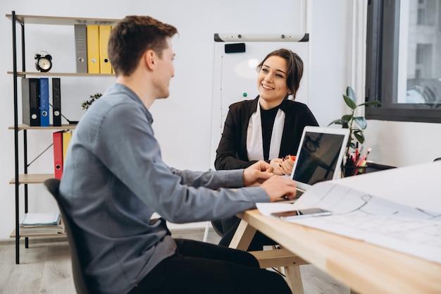 Jonge man met een interview of zakelijke bijeenkomst met werkgever. werkgever die in een modern bureaubinnenland onderzoekt