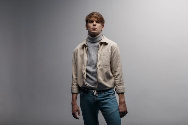Jonge man met een kapsel in een lichte stijlvolle jas in retro stijl in blauwe vintage broek in golf staat in een kamer in de buurt van een witte muur. knappe vent. moderne kleding in jeugdstijl. herenmode