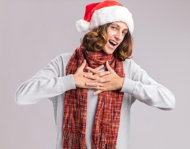 Jonge man met een kerstmuts met een warme sjaal om zijn nek, hand in hand op zijn borst, blij en vrolijk glimlachend staande over een witte muur