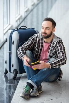 Jonge man met een koffer en paspoort klaar om te reizen.