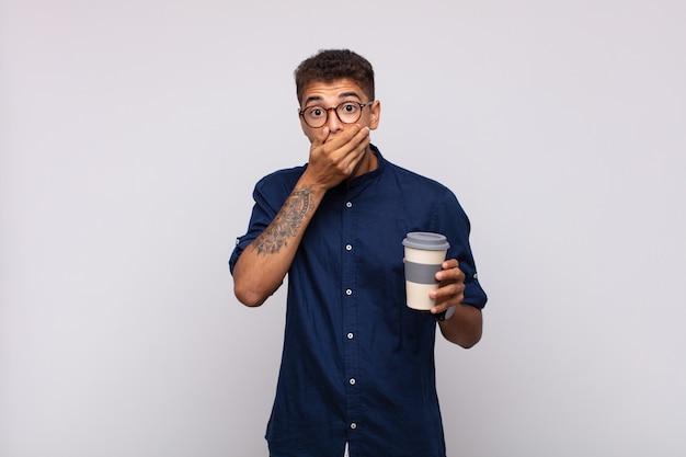 Jonge man met een koffie die de mond bedekt met handen met een geschokte, verbaasde uitdrukking, een geheim bewaren of oeps zeggen