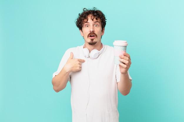 Jonge man met een koffie die geschokt en verrast kijkt met wijd open mond, wijzend naar zichzelf