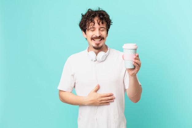 Jonge man met een koffie die hardop lacht om een hilarische grap