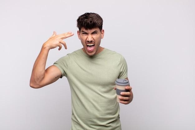 Jonge man met een koffie die ongelukkig en gestrest kijkt, zelfmoordgebaar die pistoolteken met hand maakt, naar het hoofd wijst