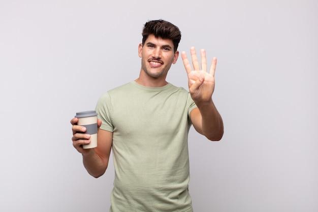 Jonge man met een koffie die vriendelijk glimlacht en kijkt, nummer vier of vierde met vooruit hand toont, aftellend