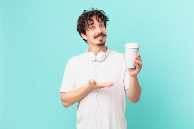 Jonge man met een koffie die vrolijk lacht, zich gelukkig voelt en een concept toont