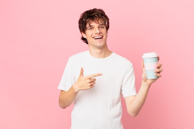 Jonge man met een koffie die vrolijk lacht, zich gelukkig voelt en naar de zijkant wijst