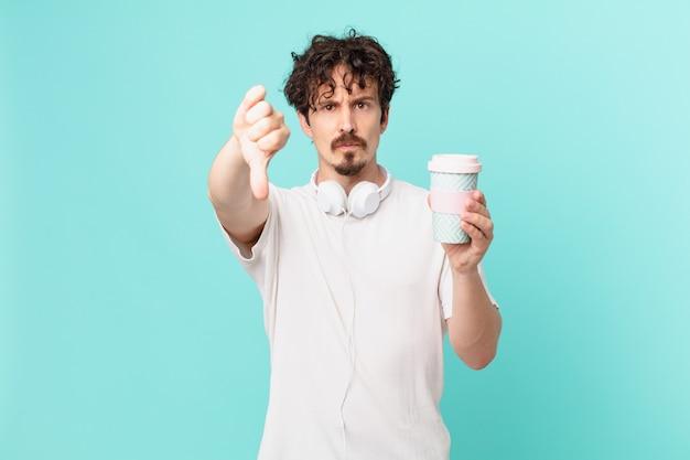 Jonge man met een koffie die zich dwars voelt en duimen naar beneden laat zien