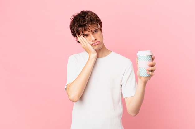 Jonge man met een koffie die zich verveeld, gefrustreerd en slaperig voelt na een vermoeiende