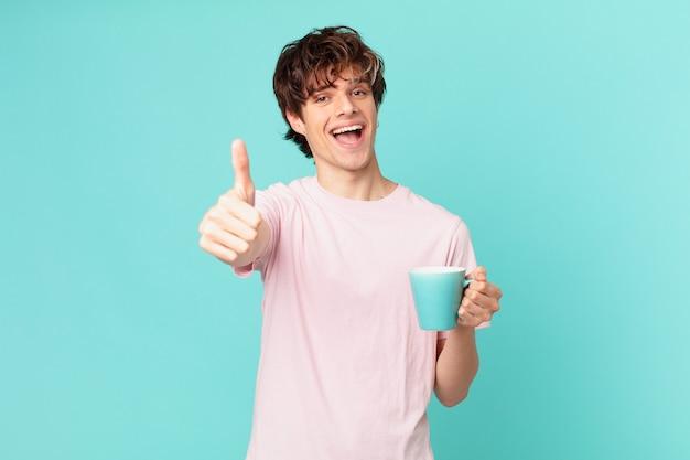 Jonge man met een koffiemok die trots is, positief glimlacht met duimen omhoog