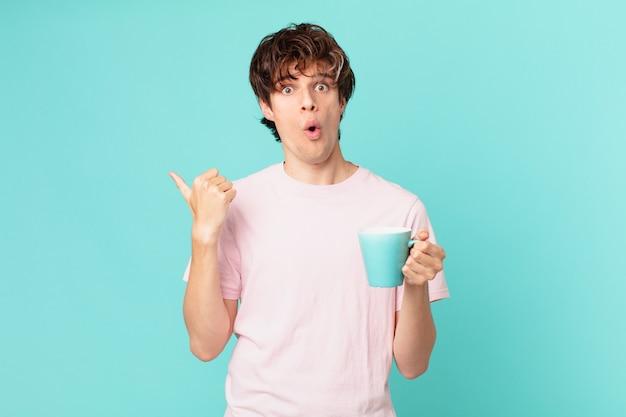 Jonge man met een koffiemok die verbaasd kijkt in ongeloof