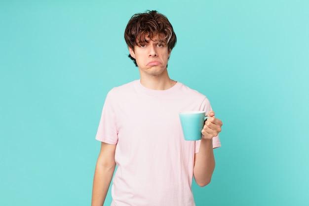 Jonge man met een koffiemok voelt zich verdrietig en zeurt met een ongelukkige blik en huilt