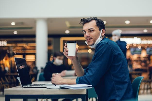 Jonge man met een kopje koffie afhaalmaaltijden zittend aan een cafétafel. foto met een kopie-spatie
