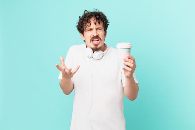Jonge man met een kopje koffie die er boos, geïrriteerd en gefrustreerd uitziet?