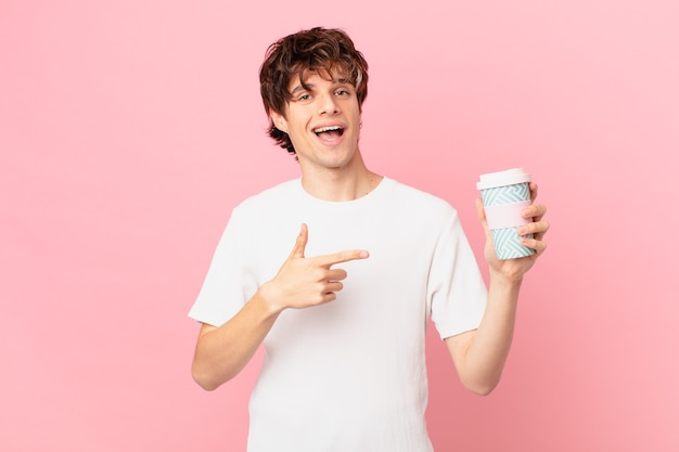 Jonge man met een kopje koffie die er opgewonden en verrast uitziet en naar de zijkant wijst