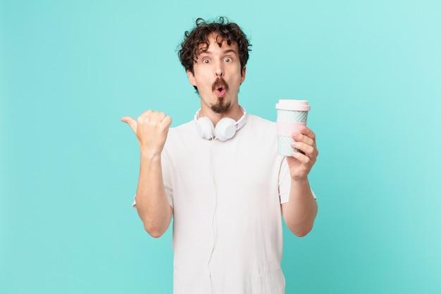 Jonge man met een kopje koffie die verbaasd kijkt in ongeloof