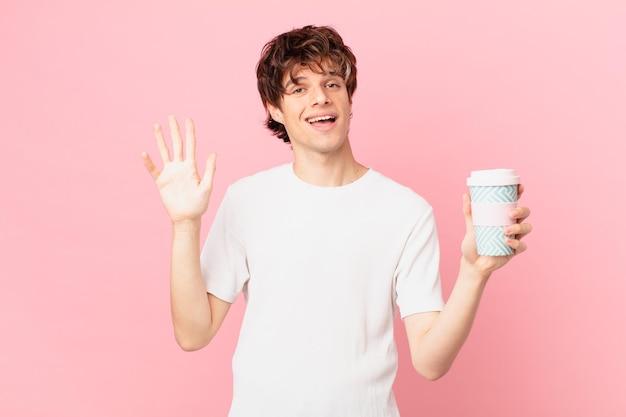 Jonge man met een kopje koffie die vrolijk lacht, met de hand zwaait, je verwelkomt en begroet?