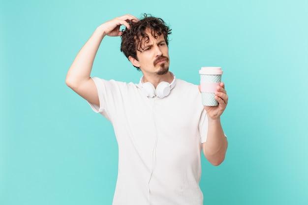 Jonge man met een kopje koffie die zich verbaasd en verward voelt, hoofd krabben