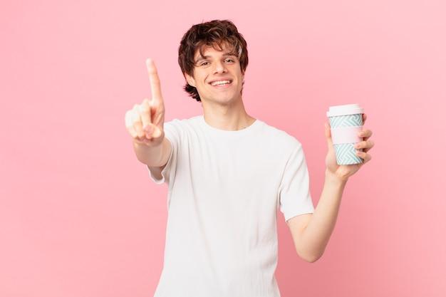 Jonge man met een kopje koffie glimlachend trots en vol vertrouwen nummer één maken