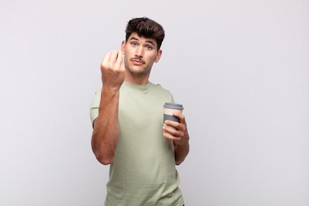 Jonge man met een kopje koffie of een geldgebaar, die je vertelt je schulden te betalen!