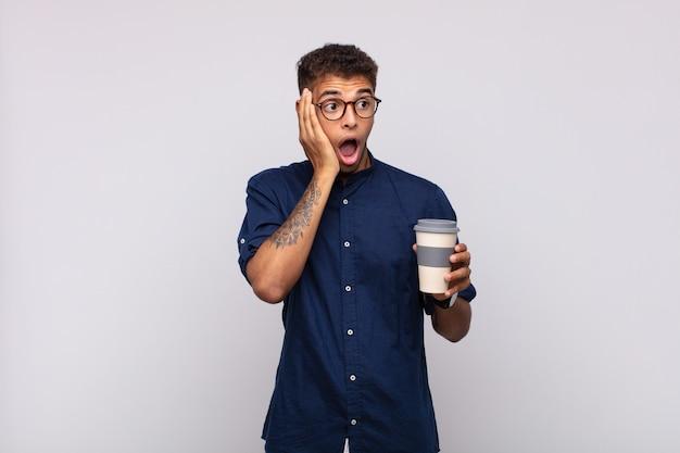 Jonge man met een kopje koffie voelt zich blij, opgewonden en verrast, opzij kijkend met beide handen op het gezicht