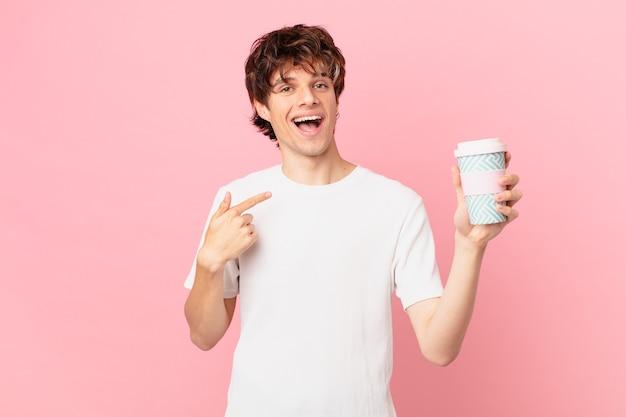 Jonge man met een kopje koffie voelt zich gelukkig en wijst naar zichzelf met een opgewonden