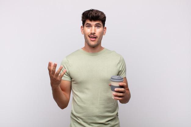 Jonge man met een kopje koffie zich blij, verrast en opgewekt voelen, glimlachend met een positieve instelling, een oplossing of idee realiseren