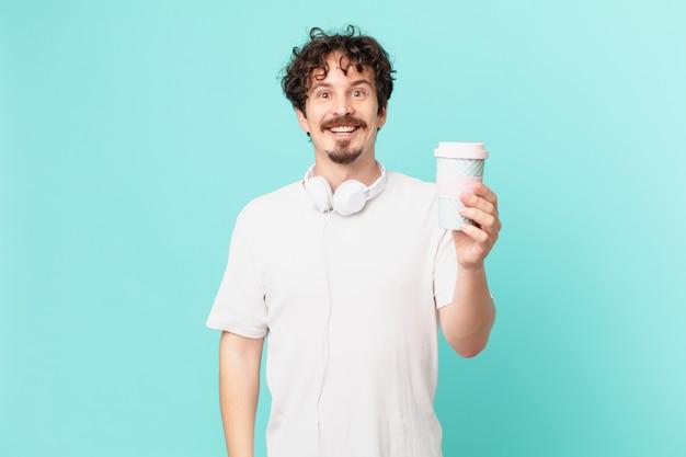 Jonge man met een kopje koffie ziet er blij en aangenaam verrast uit?