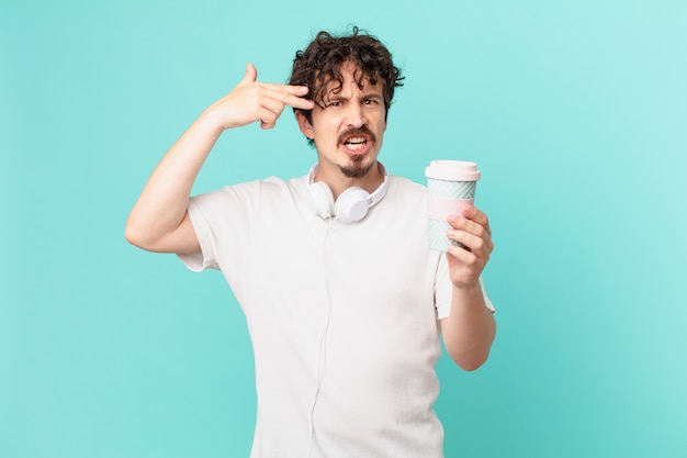 Jonge man met een kopje koffie ziet er ongelukkig en gestrest uit, zelfmoordgebaar maakt pistoolteken