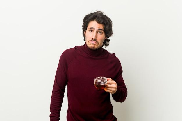 Jonge man met een kopje thee haalt schouders en open ogen verward.