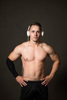 Jonge man met een koptelefoon op sportschool