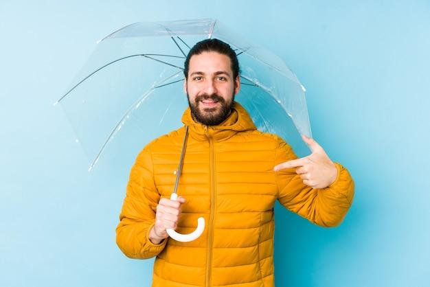 Jonge man met een lang haar kijkt met een paraplu geïsoleerde persoon met de hand wijzend naar een shirt kopie ruimte, trots en zelfverzekerd