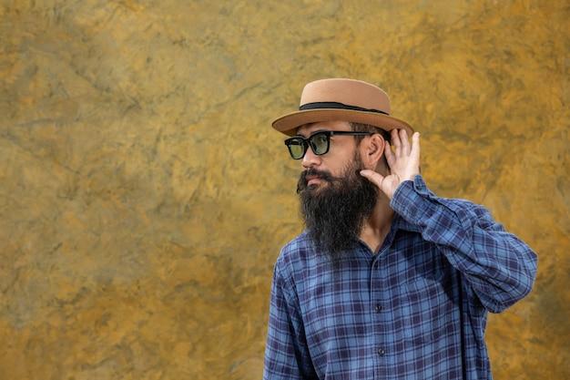 Jonge man met een lange baard met een hoed en een bril
