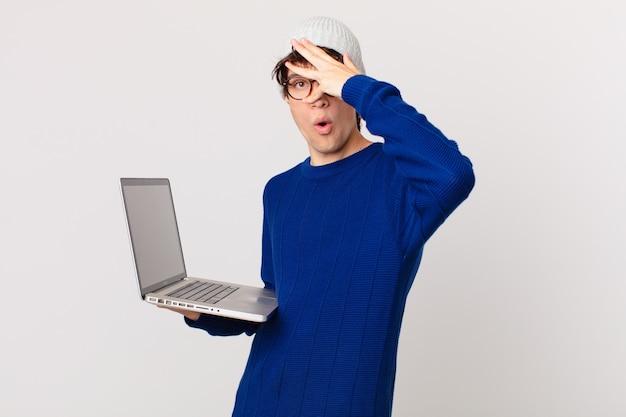 Jonge man met een laptop die er geschokt, bang of doodsbang uitziet en zijn gezicht bedekt met de hand