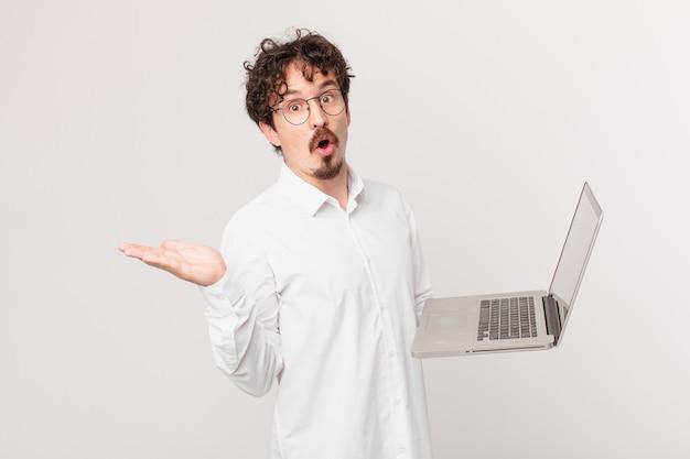 Jonge man met een laptop die er verrast en geschokt uitziet, met open mond terwijl hij een voorwerp vasthoudt