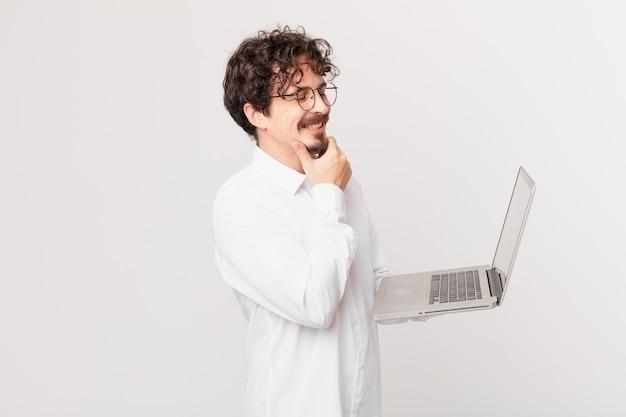 Jonge man met een laptop die lacht met een vrolijke, zelfverzekerde uitdrukking met de hand op de kin
