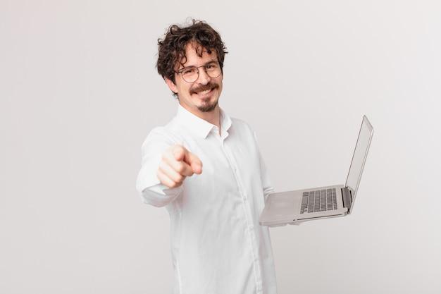 Jonge man met een laptop die naar de camera wijst en jou kiest