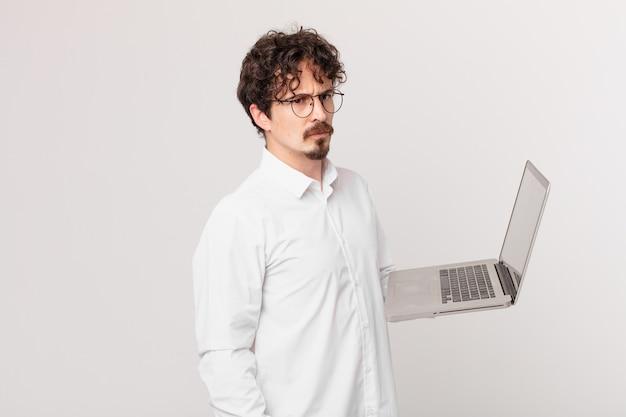 Jonge man met een laptop die zich verdrietig, overstuur of boos voelt en opzij kijkt
