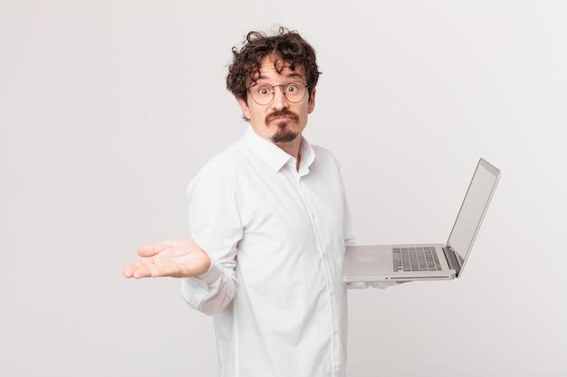 Jonge man met een laptop die zich verward en verward en twijfelt