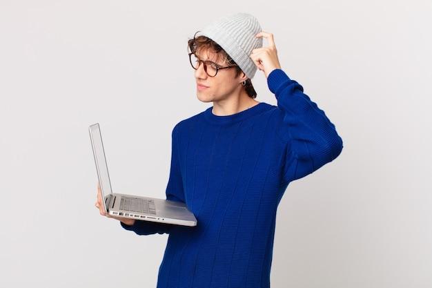 Jonge man met een laptop die zich verward en verward voelt, hoofd krabben