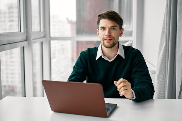 Jonge man met een laptop in een pak werken op kantoor en thuis op een van een raam, online interviewen