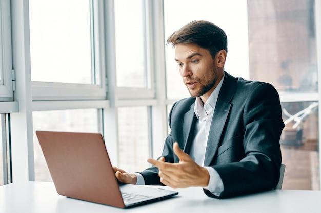 Jonge man met een laptop in een pak werken op kantoor en thuis